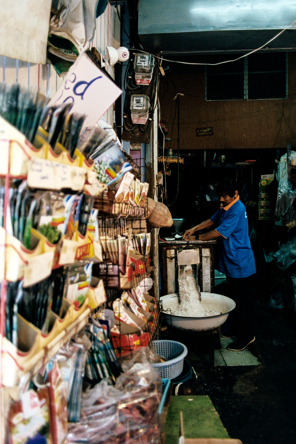 A shop worker shreds coconut at a produce market.