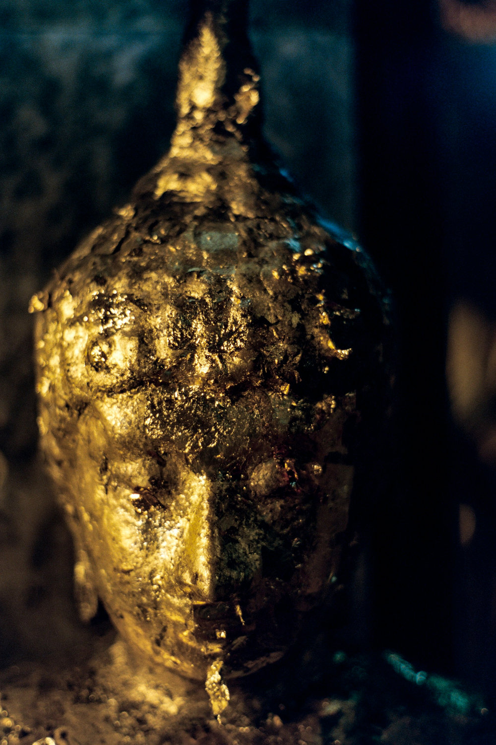 A Buddha statue covered in flaky gold leaf. Visitors press gold leaf into the Buddha's face, resulting in this buildup.