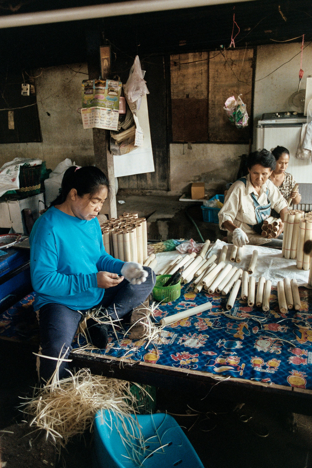 A woman prepares kralan: a traditional snack of sticky rice and coconut, packed inside a hollow bamboo stick.