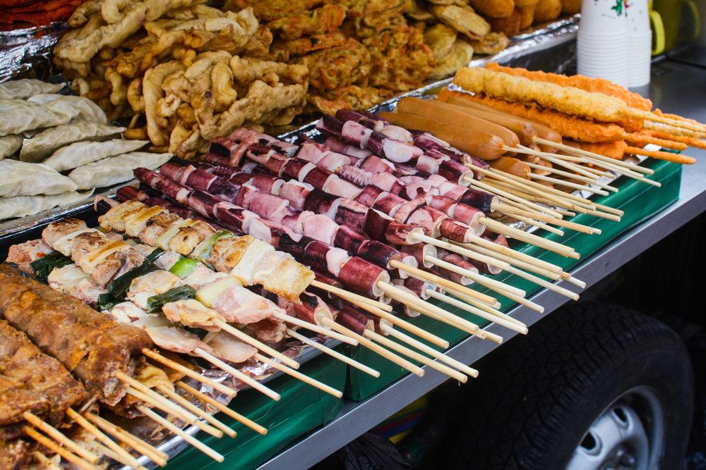 Racks of skewers piled up on a street vendor's cart. Chicken, pork, octopus, fishcake and dumplings.