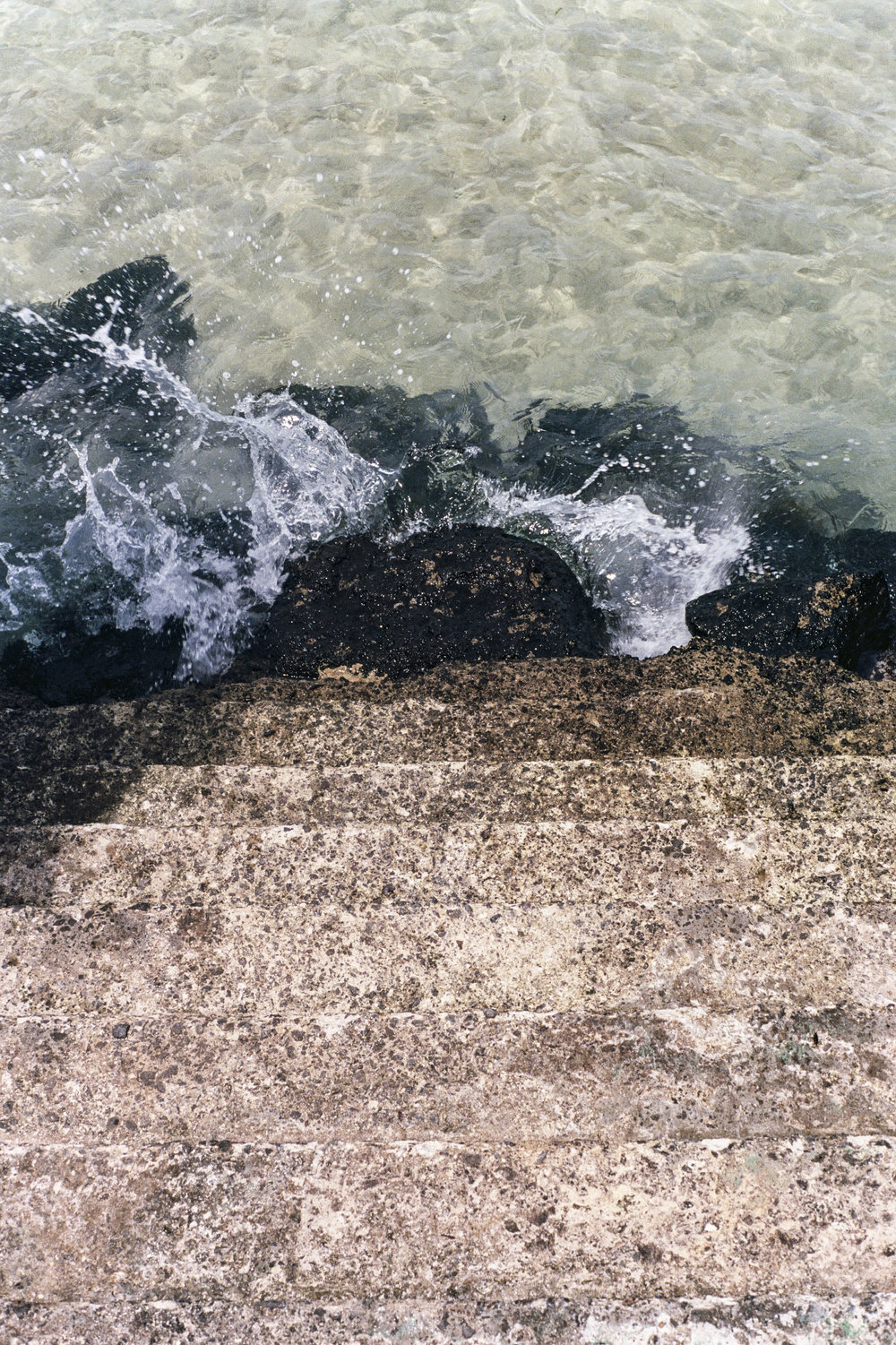 Waves crash on the steps of Cafe Delmoondo at high tide.