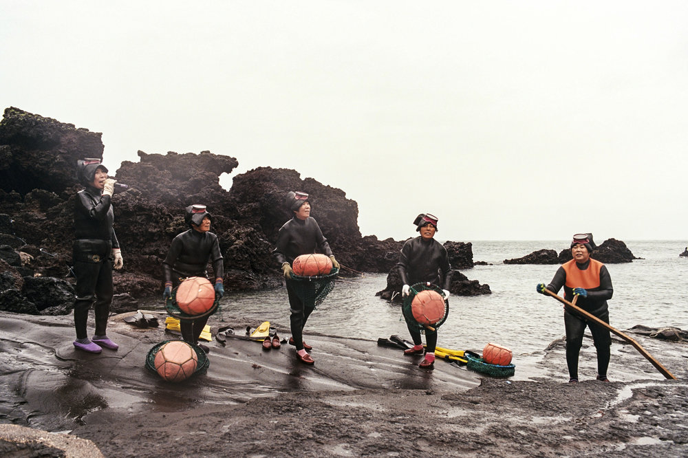 A group of Haenyeo, Jeju's famous diving women, sing for tourists before a fishing demonstration. They dive up to depths of ten meters without breathing equipment, wearing only wetsuits and diving goggles. Most divers are over the age of sixty, with some as old as eighty five.