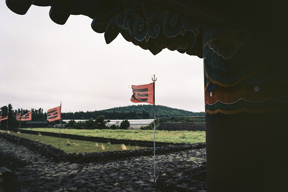 Flags fly atop the city wall surrounding a traditional village.