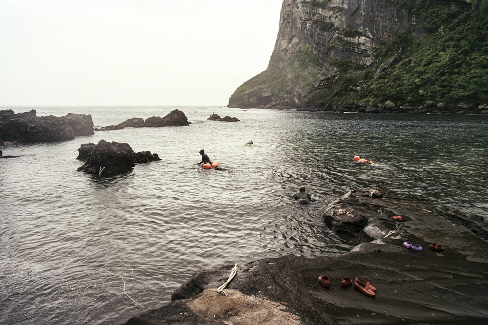 Divers leave their shoes and swim out into the cove.
