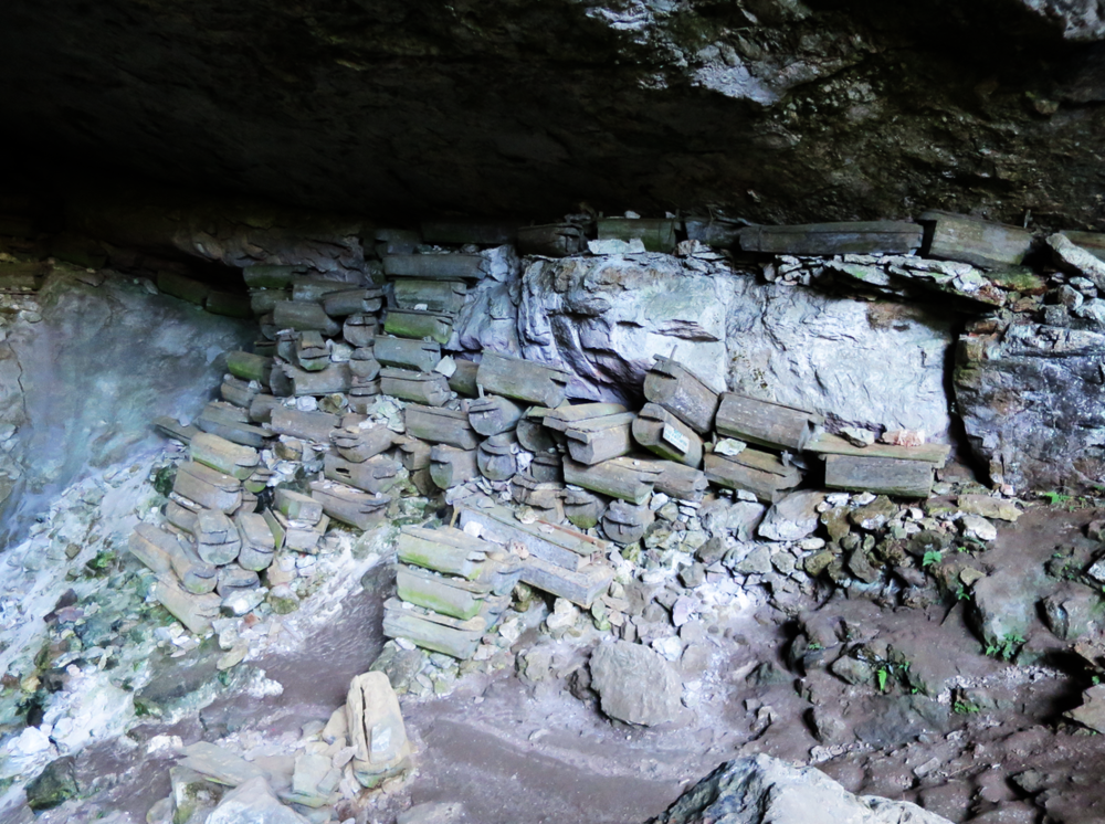 Stacked coffins in the cave mouth.