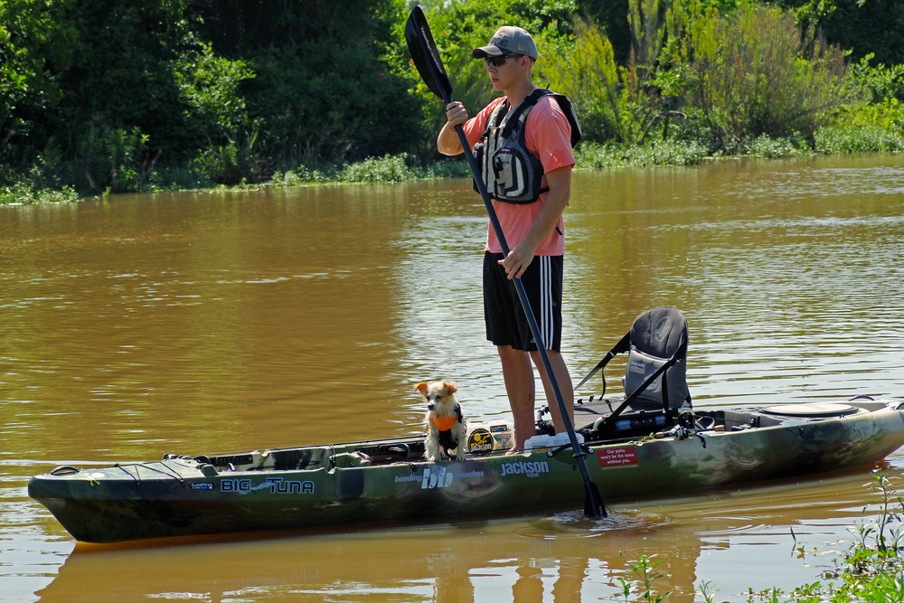 Clint Taylor with his dog Pup in the UnderDog life jacket from MTI Adventurewear and Clint with his Jackson Kayak Big Tuna, Bending Branches Angler Ace, and MTI Adventurewear Dio F-Spec