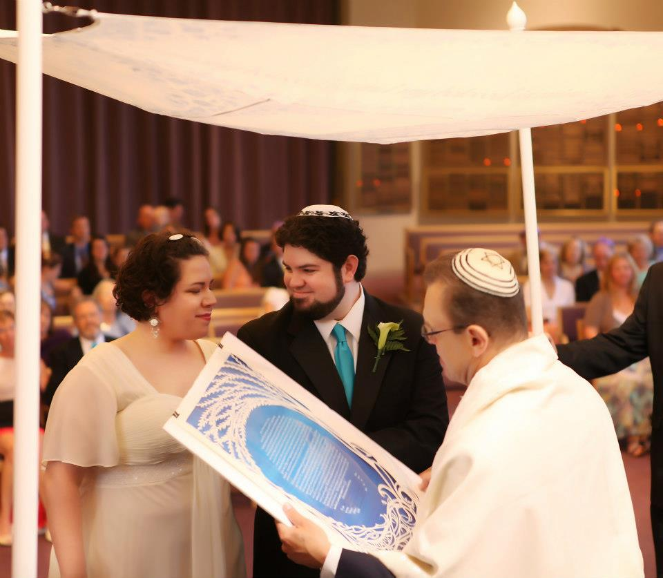 Couple reading Jewish Marriage document at wedding