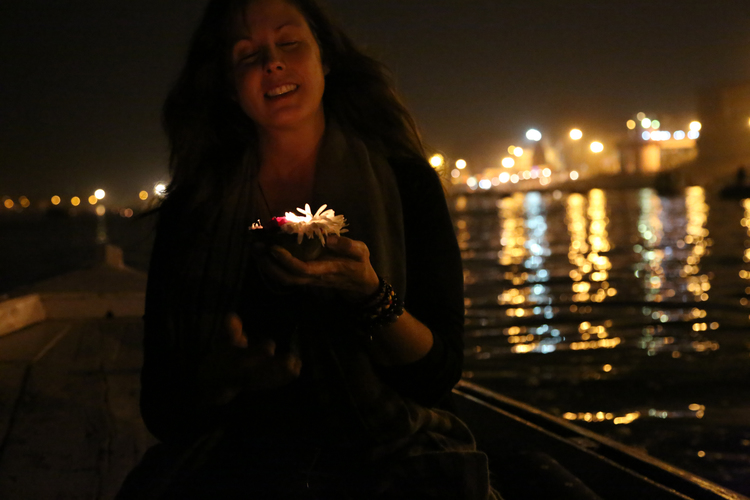 Michelle Larson  - I feel most ALIVE when I am immersed in a foreign place; absorbing the energy, witnessing the devotion, experiencing the culture in a meaningful way. This photo was taken of me in Varanasi, India. I was in a row boat on the sacred Ganges River. The candle and flowers are an offering to the Gods; a wish or a prayer. I was mid-wish as this photo was taken... then I placed the candle in the water and watched it float to meet the hundreds of other flames, with their reflections dancing while they manifested.