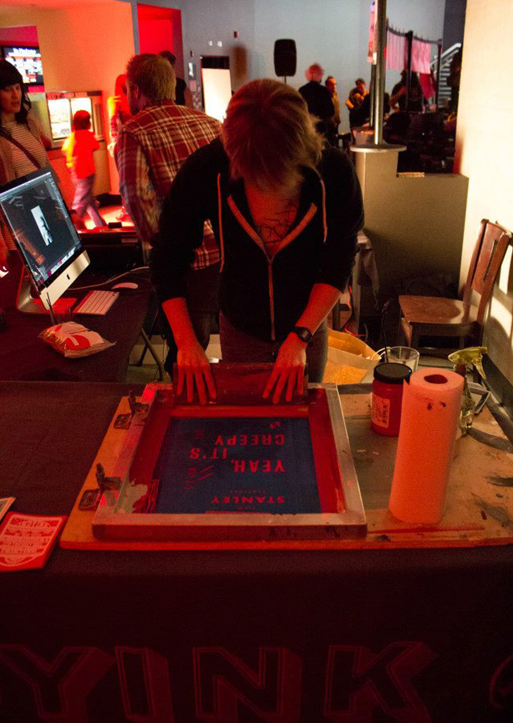 A woman screen prints onto a photograph at the Stanley Film Festival kick-off event.