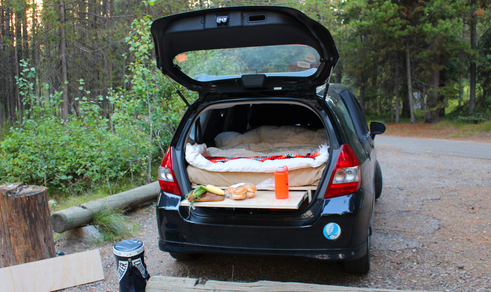 A Honda Fit with a wooden bed in the trunk, hand-constructed by Adam Jeffers.
