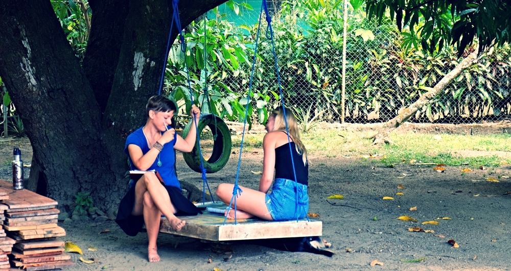 Dixie holding one-on-one project check-in meetings with a student on the tree-swing.