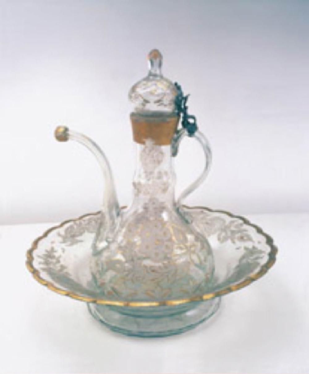 Leğen ve ibrik, kristal üzeri çiçek ve dallarla süslenmiş, yapraklar arası altın yaldızlıdır. Leğen ve ibrik aynı desende olup, ibriğin kapağı gümüş menteşe ile kulpuna sabitlenmiştir. Leğen çapı: 34,5 cm, ibrik yük: 36 cm. Topkapı Sarayı Müzesi Koleksiyonu. Env. No: Leğen 34/ 1812, İbrik 34/1811.