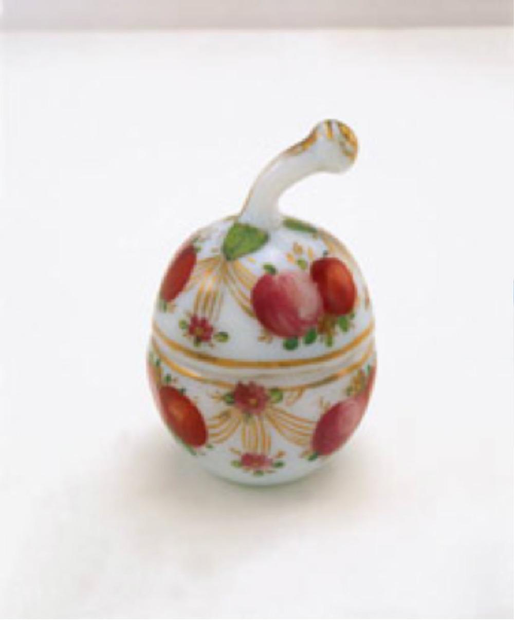 Beyaz opalinden, elma formunda kapaklı ve tutamağı elma sapı şeklinde sakızlık, üzeri kırmızı ve pembe renkli meyvelerle süslenmiş meyveler arası altın yaldız girlandlar ve çiçeklerle bağlanmıştır. Y: 11 cm, Topkapı Sarayı Müzesi Koleksiyonu. Env. No: 34/1289.