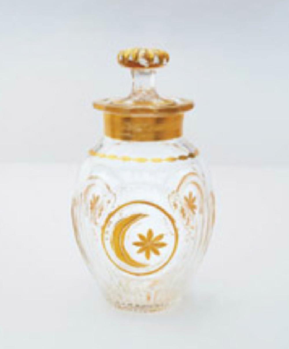 Kapaklı kristal kavanoz, altın yaldızlı pafta içinde ay-yıldız desenlidir. Boyun altın yaldızlıdır. Kapak tutamağı kesme tekniği ile süslenmiş ve altın yaldızlıdır. Y: 21 cm, Topkapı Sarayı Müzesi Koleksiyonu. Env. No: 34/618.