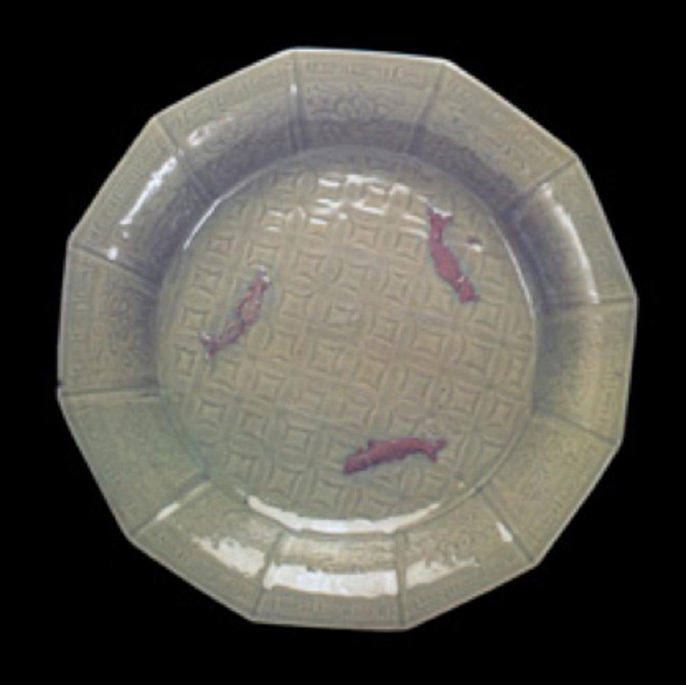Seladon tabak. Ming Hanedanlığı, 15.yüzyıl. Ortasındaki kabartma balık desenleri sırsız bırakıldığı için kırmızı renkte.