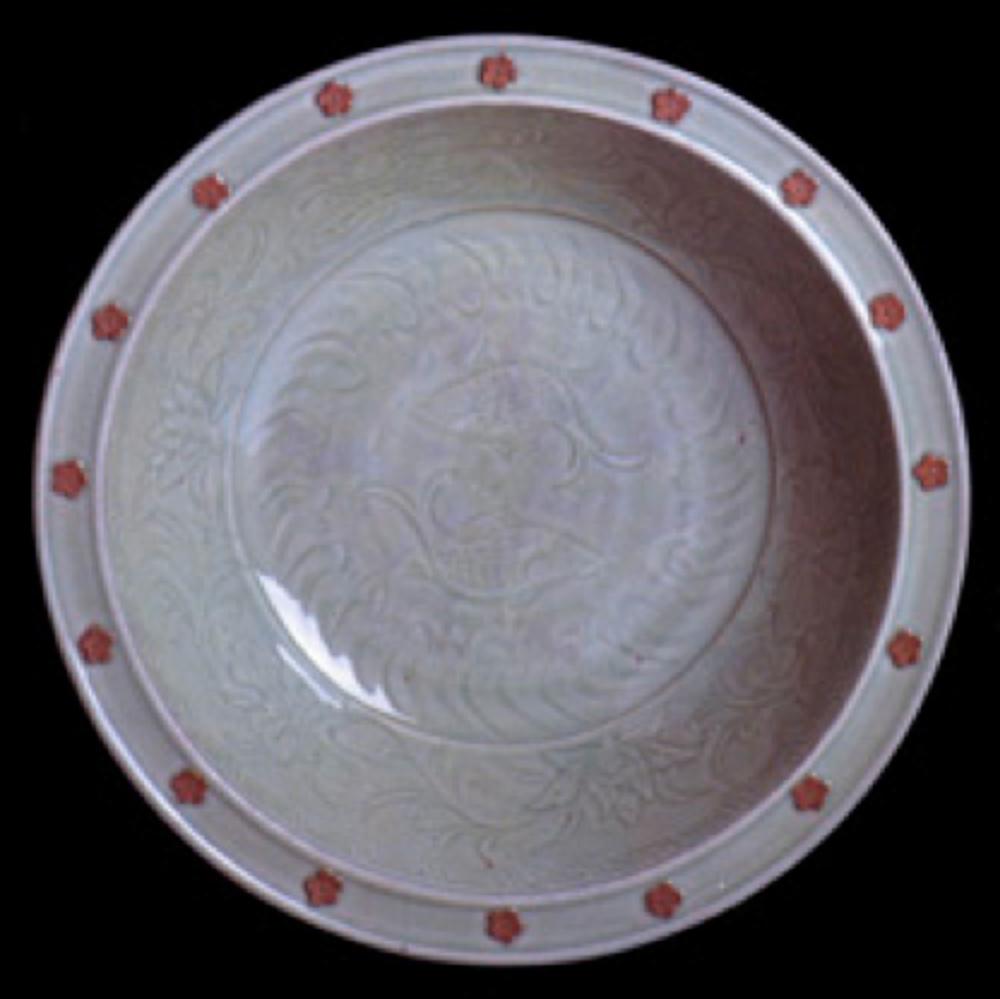 Seladon tabak. Yuan Hanedanlığı, 14.yüzyılın ilk yarısı. Ortası çift balık ve radyal dalgalar, kenarı lotus çiçekleriyle bezeli. Ağız kenarında eşit aralıklarla dizilmiş çiçek motiflerinin üstü sırsız bırakılarak kontrast oluşturulmuş.