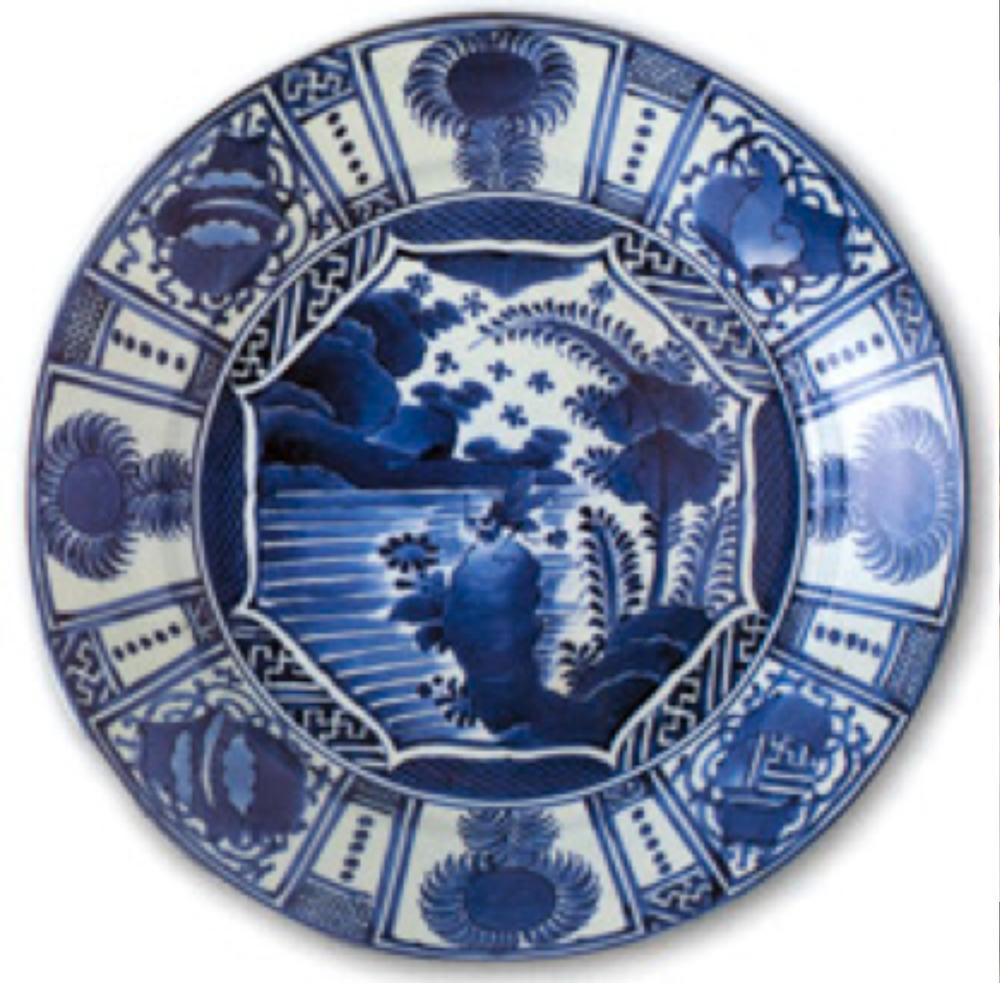 1670-1690 yıllarına tarihlenen, mavi-beyaz renklerde, kayalıklar, göl manzarası ve amblemlerle süslenmiş Japon İmarisi tabak.