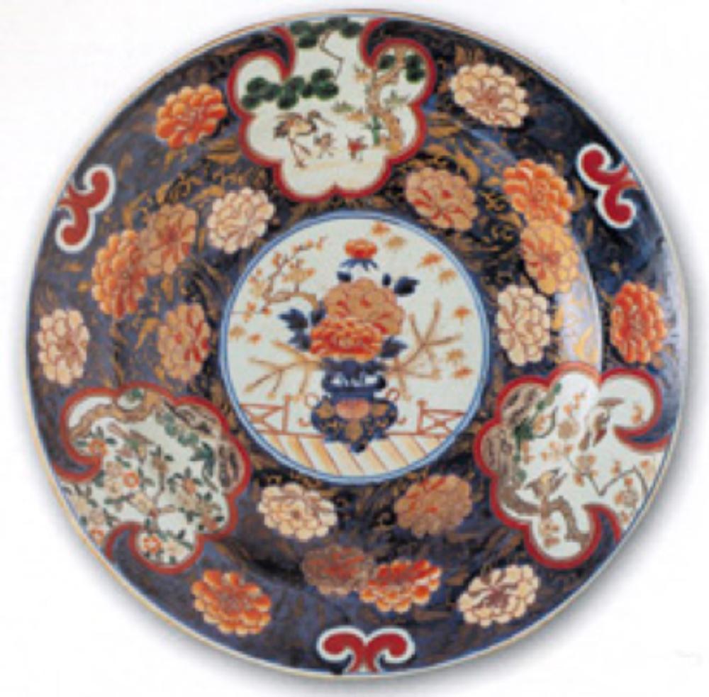 1700-1740 yıllarına tarihlenen, ortasında vazo içinde çiçekler, kenarında beyaz zeminli dilimli üç pafta içinde kuşlar ve bitkiler ile süslenmiş Japon İmarisi tabak.