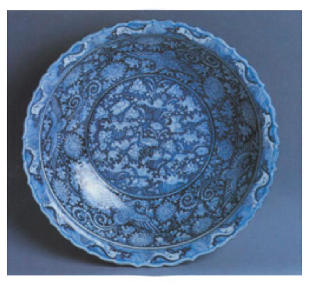 Mavi-beyaz tabak, Yuan Hanedanı, 14. yüzyıl ortaları. Ortasında turna ve lotus kenarında anka kuşları ve krizantemler, ağızda dalga bordürü vardır. Kobalt mavisi iyi rafine edilmediği için beneklidir.
