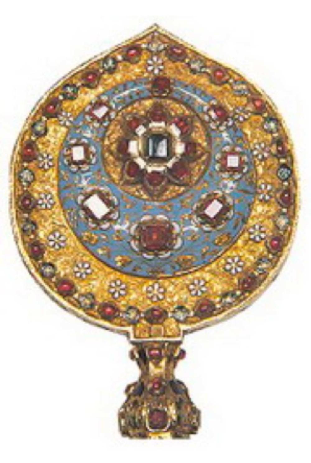 Mücevherli altın yelpaze sapı. 17. yy. ortaları, Osmanlı. Uzunluk : 21cm, çap : 8.5cm , T.S.M. 2/3565 Alem biçiminde her iki yüzü mineli, yakut ve zümrüt bezelidir. Altın paftaların arasında kenarlara tüy takmak için kanal oluşturulmuştur. Milfiori cam çubuğuntepesinde bir firuze vardır.