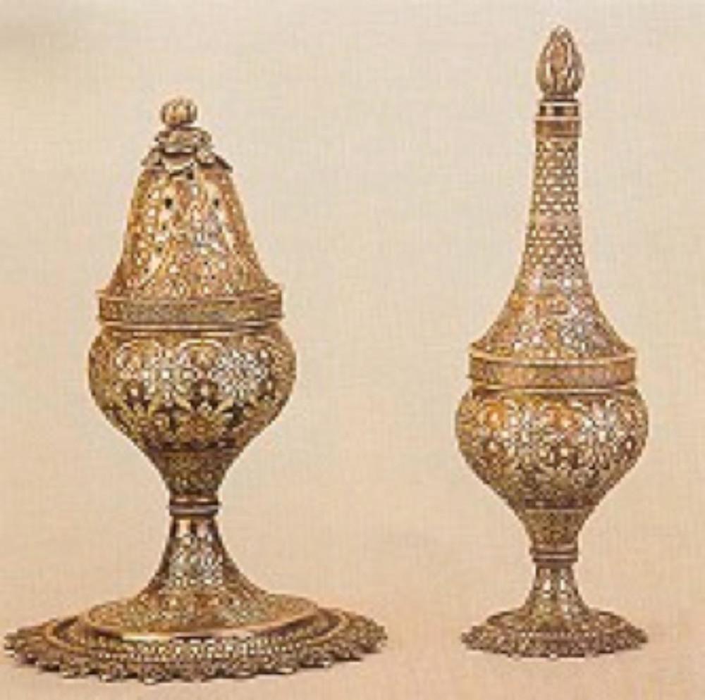 GÜLABDAN&BUHURDAN TAKIMI Sultan Abdülaziz (1861-1876) dönemi ürünü takımda her iki parçanın gövdeleri de kaidelerine vidalanarak oturuyorlar. Buhurdan kapağı ajur işçilikli ve oturtma kozalak tutamaklı, gülabdan emziği vidalı bağlantılıdır. Kumlama tekniği uygulanmış zemin, badem kabaralı motifler ve yatay bantlarla süslenmiştir. Gülabdanın yüksekliği 19 cm, buhurdanın yüksekliği 18 cm'dir.