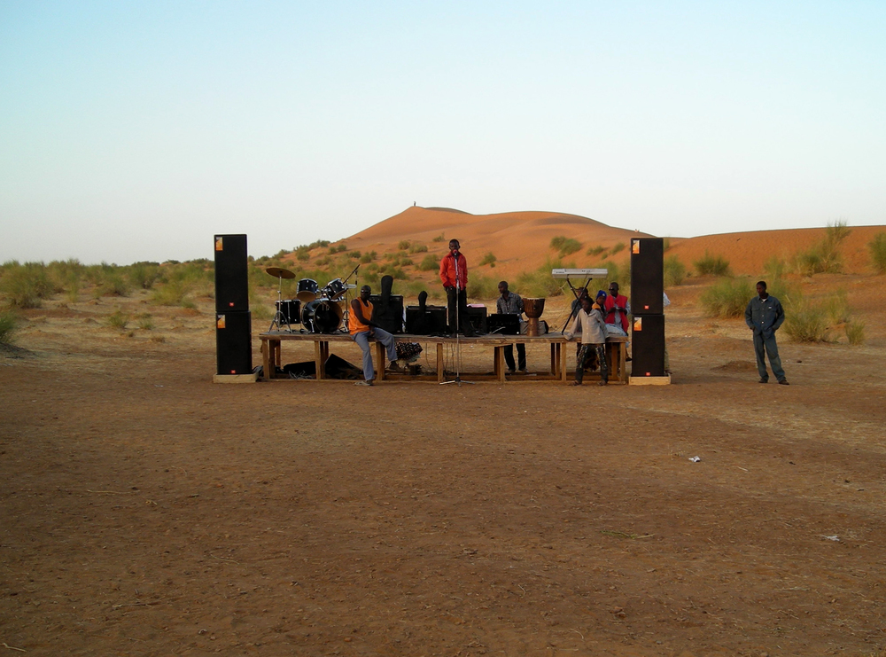 Nasser Maïga making a first soundcheck at the Sweden/Mali voices festival in Koïma, jan 2010. The red dunes of Koïma in the background.
