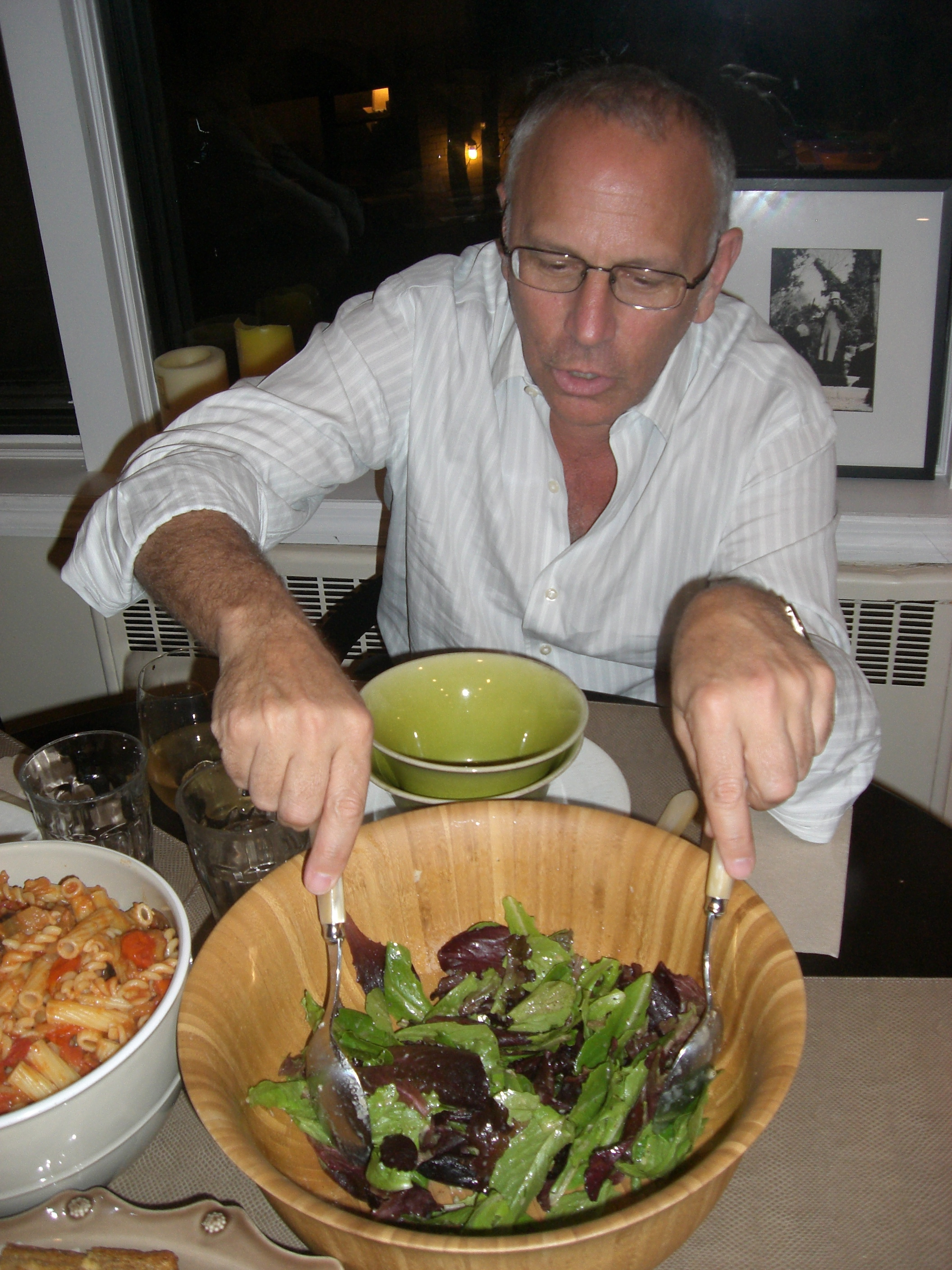 Dad serving salad at our vegan pasta dinner.