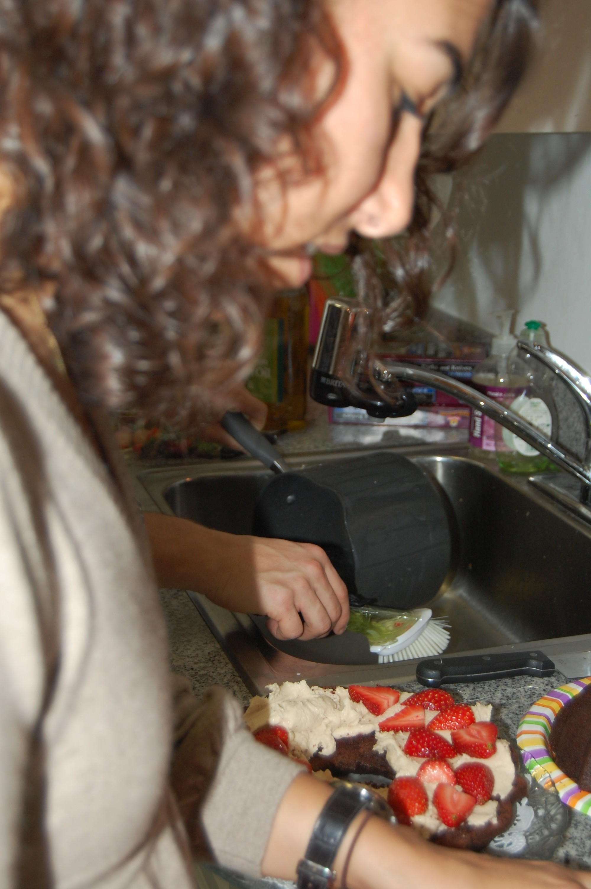 Liza is preparing the last minute touches to her vegan chocolate strawberry cake.