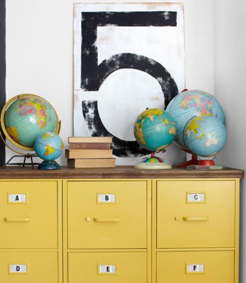 How cool is this collection of world globes simply displayed on top of a chest of drawers? Image source:  Country Living