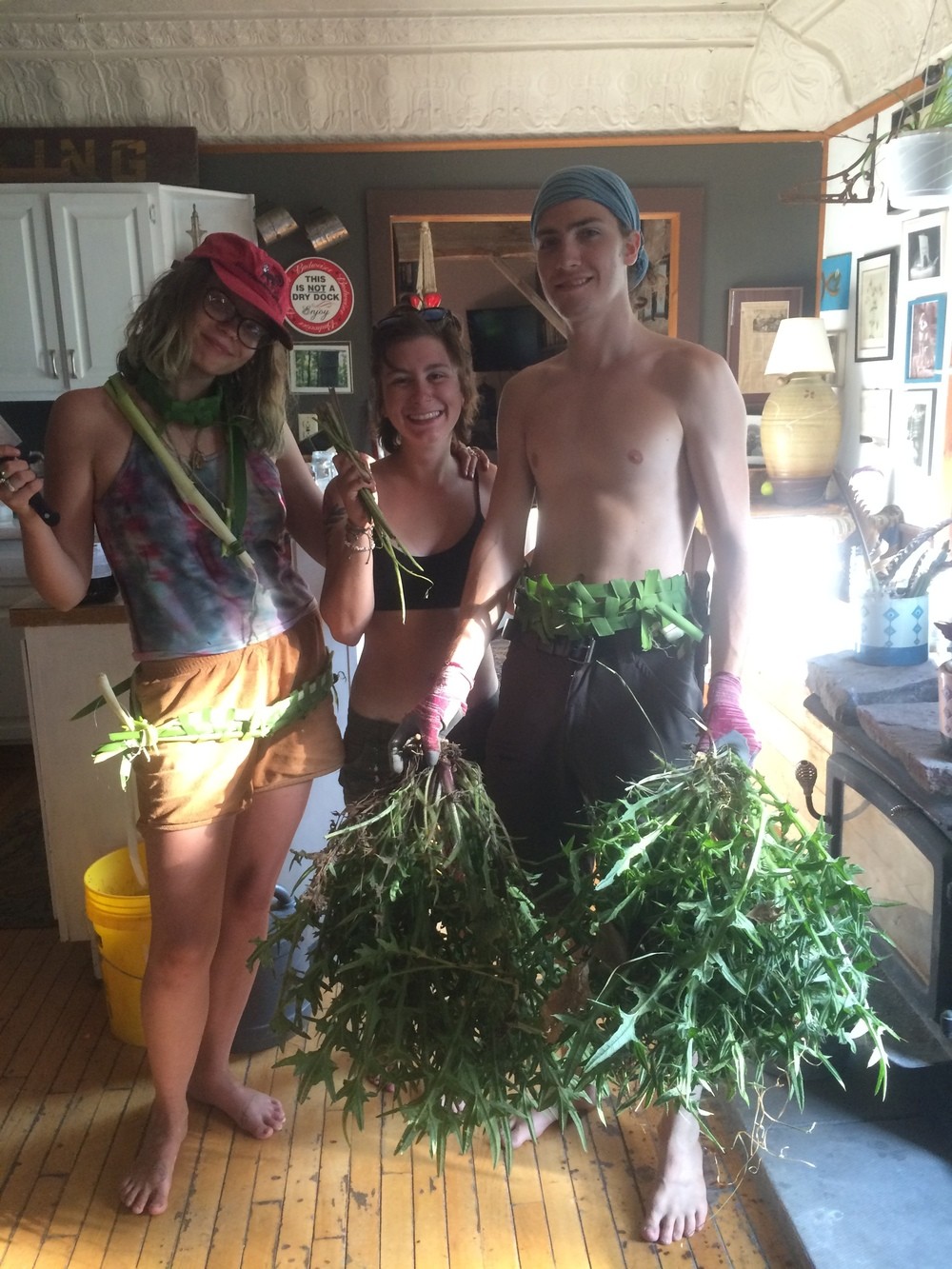 Students (from left) Nina, Steph and Levi display cattails and thistle harvested from the property.