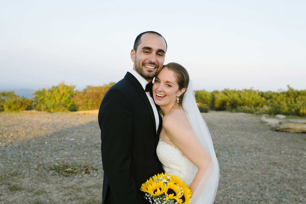 Bride and Groom smiling on top of Wachusett Mountain on their wedding day