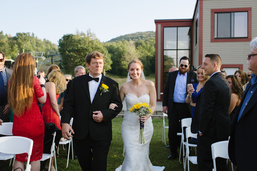 Bride walks down the aisle with her father on her wedding day with Wachusett Mountain in the background