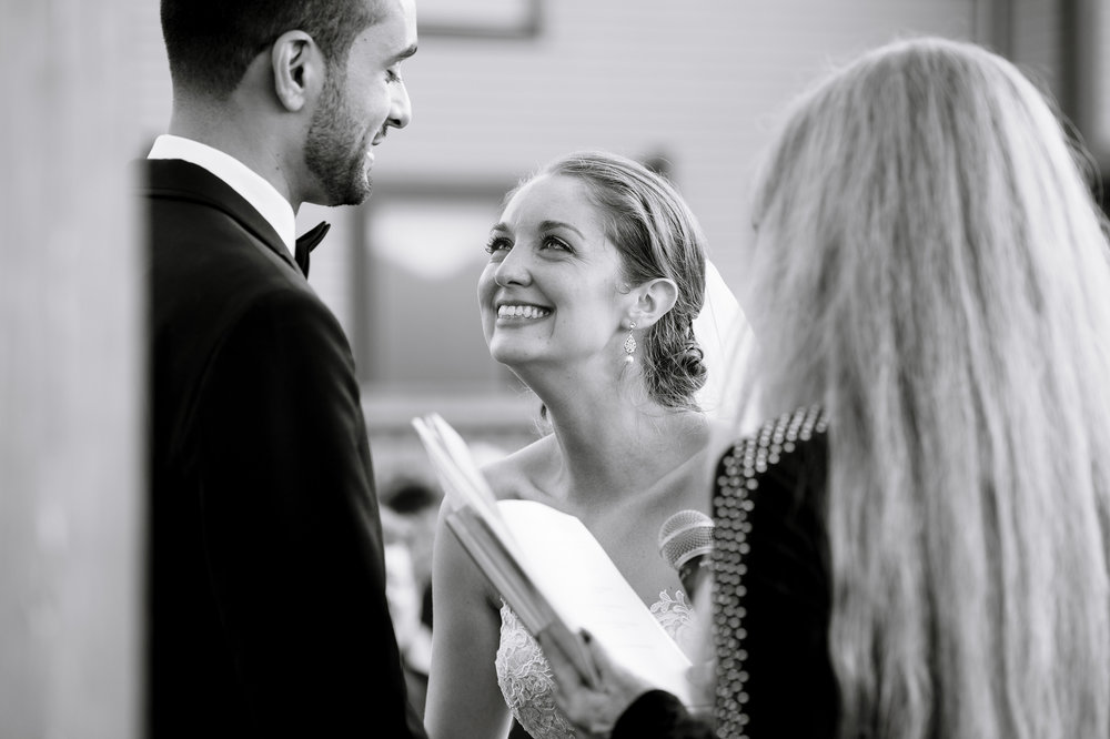 Bride smiling during her vows during a candid moment at her wedding ceremony