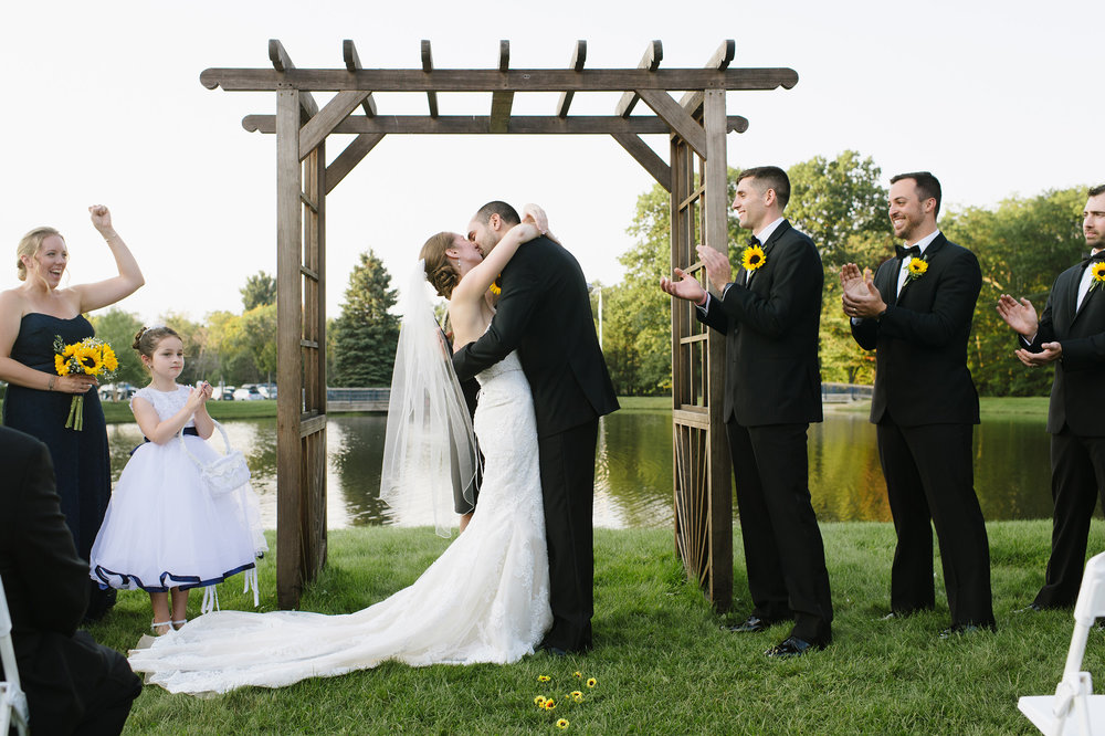 Bride and groom have their first kiss during their wedding ceremony at Wachusett Mountain Ski Area
