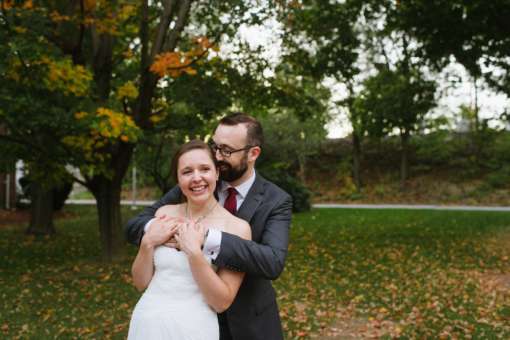 Bride smiling outside The Griffin Museum of Photography on her wedding day in the autumn