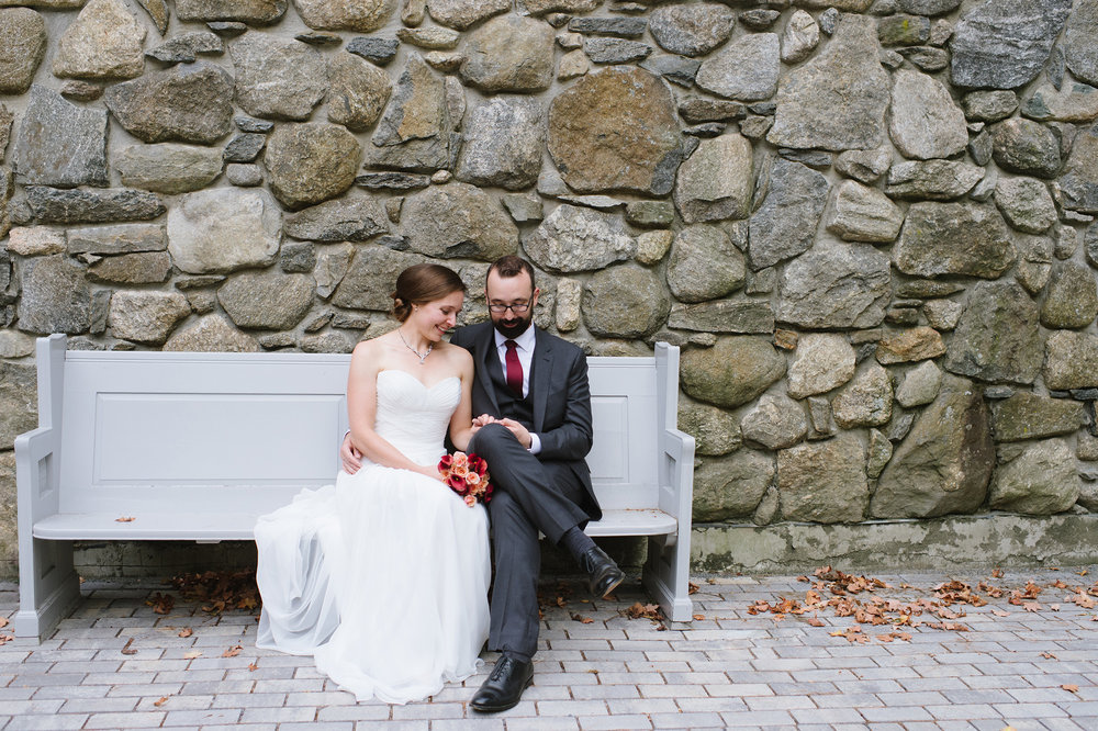 Bride and Groom outside the Griffin Museum of Photography sitting on bench and enjoying a candid moment together