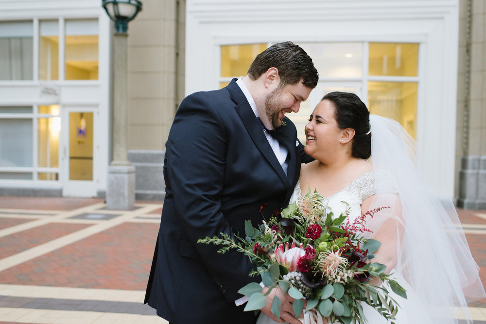 Bride and Groom laughing out in front of the Boston Harbor Hotel on their wedding day