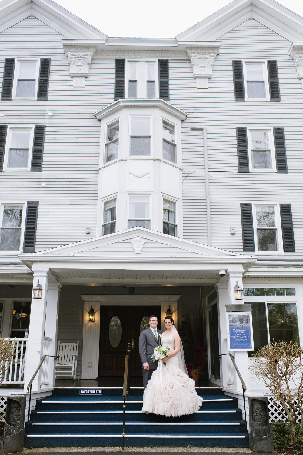 At the Nonantum Resort, Kennebunkport, Maine a Bride and Groom stand inside the entryway