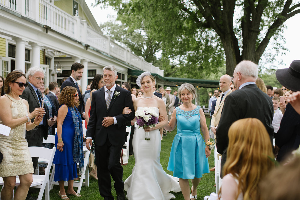 Bride walking down the aisle at The Country Club, Brookline with her parents