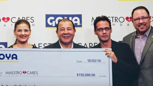 Mark Anthony and his Maestro Cares partner Henry Cardenas accept a check from Goya president Bob Unanue.