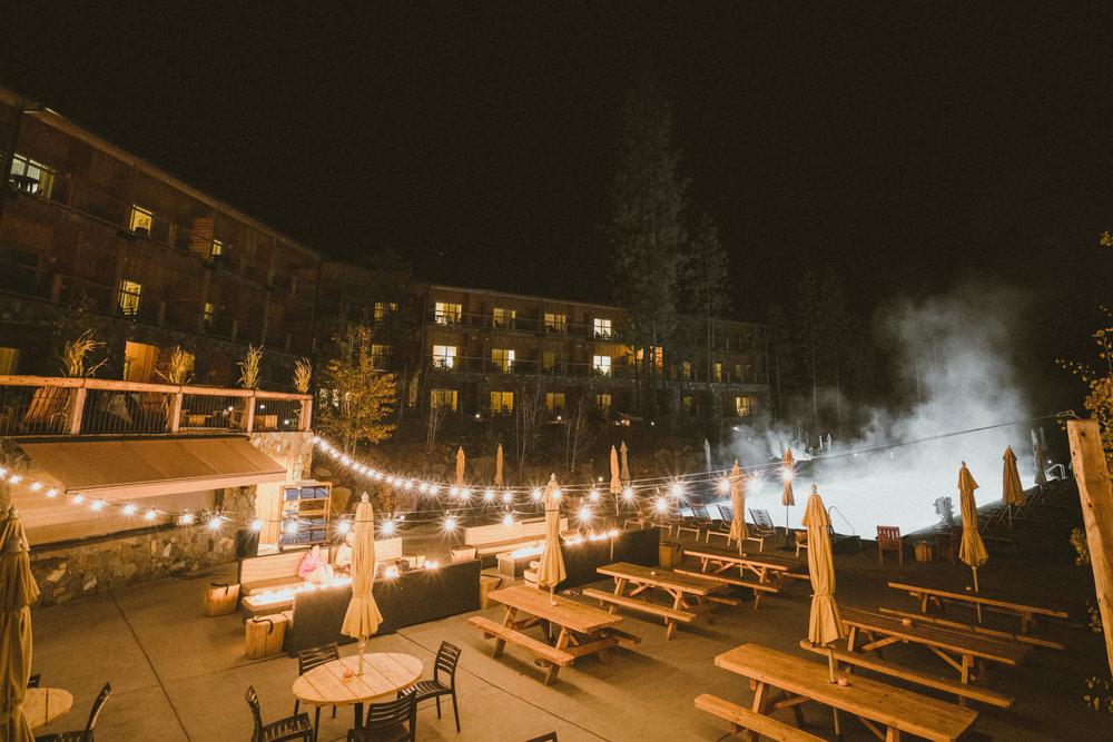 Campfire and pool area at night at Rush Creek Lodge