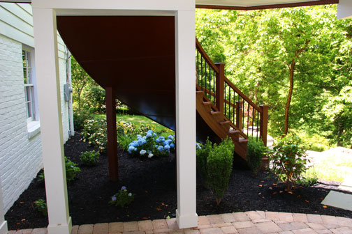 Curved Laminated Stair Stringers and Curved Trex Transcend Stair railing installed by Highland Renovations in Maryland.