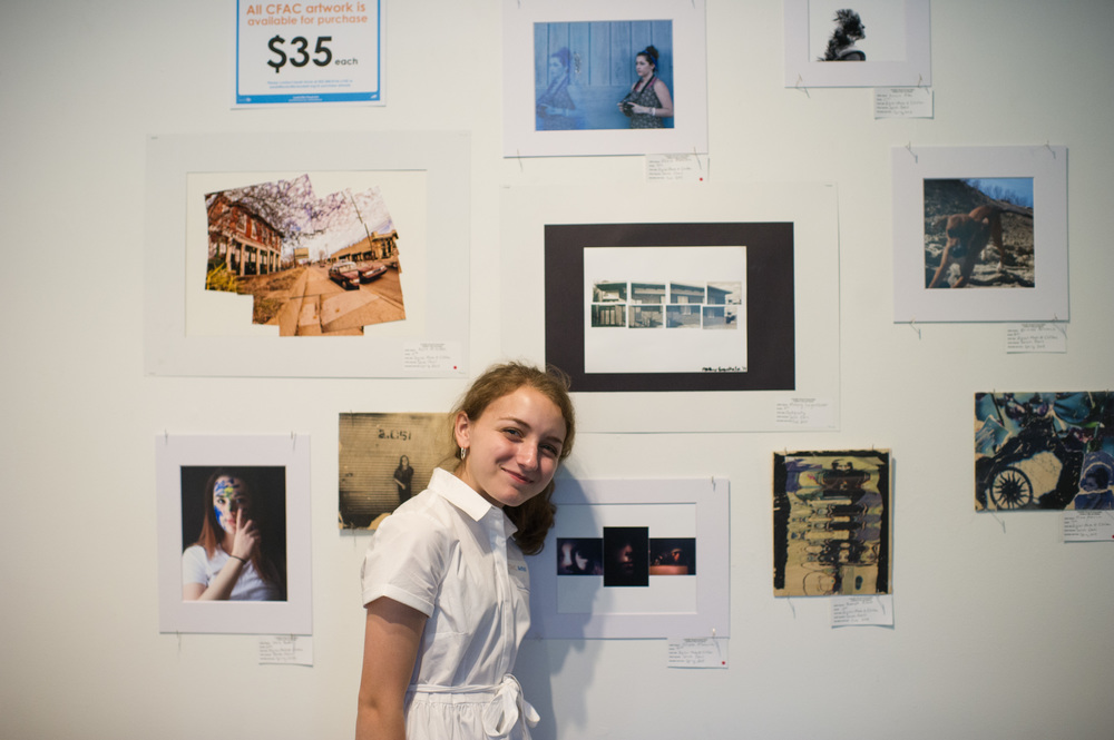 Olivia Marcum stands with the work she created in Digital Photography with Sarah Davis
