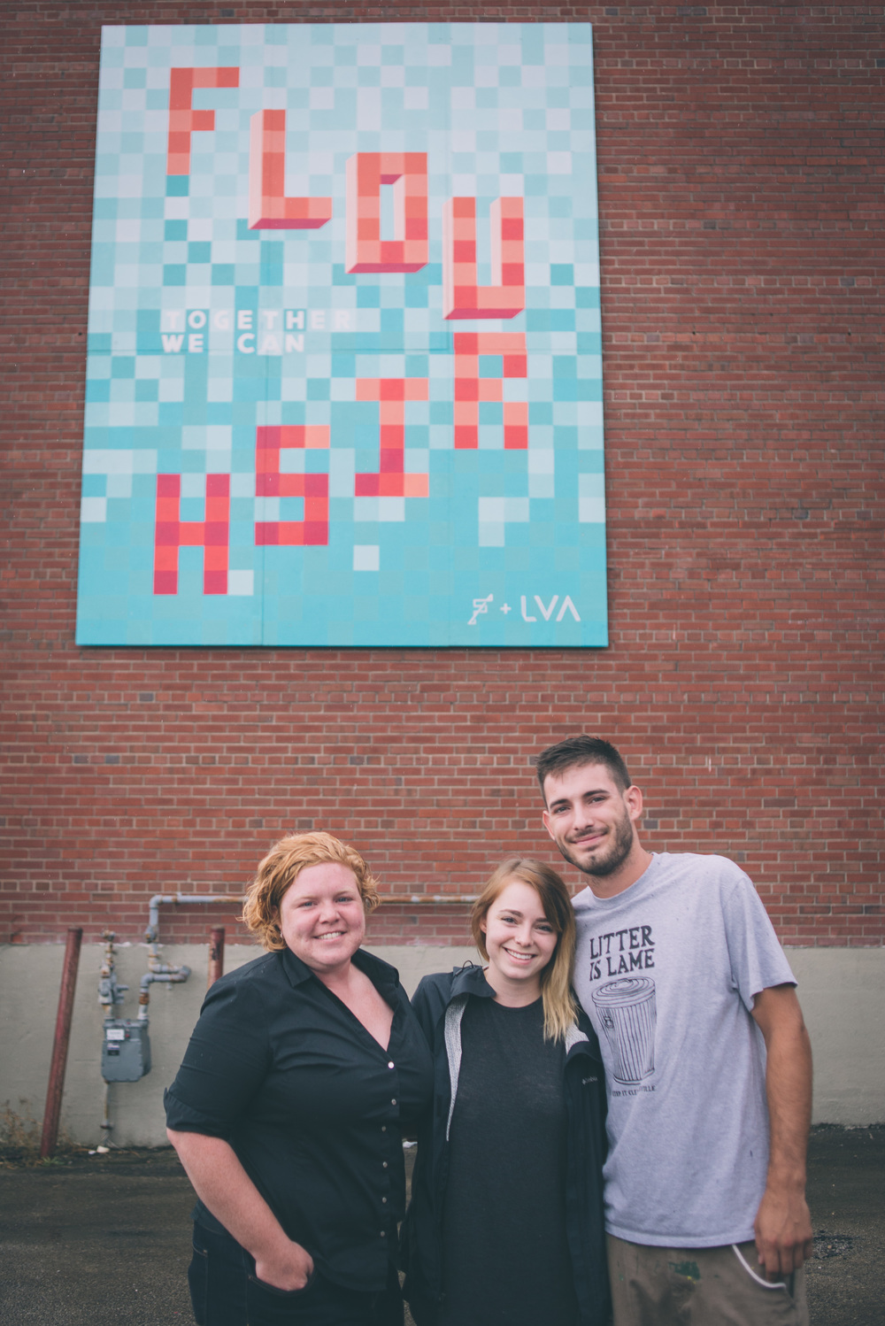 "Ashley Brossart, Ashley Trommler, Branden McClain in front of ""Flourish"""