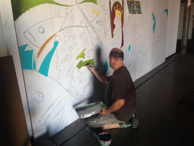 Casey McKinney at work on his mural.