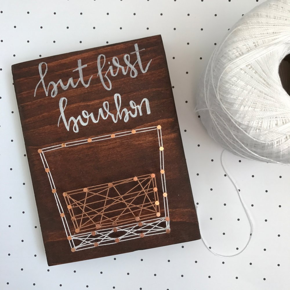 """But First, Bourbon"" by Wood & Twine, 6x8in, wood, string (2016), $35 