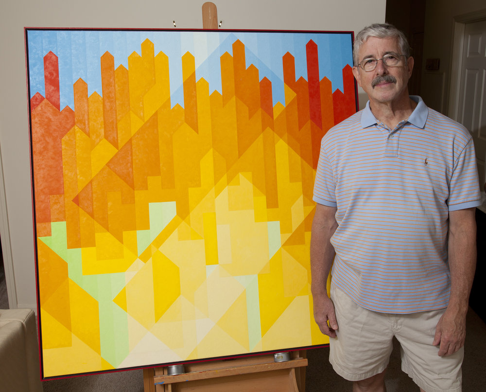 Burcaw standing next to one of his sold paintings.