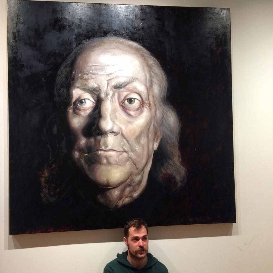 "Artist, Jordan Lance Morgan in front of his painting ""Rising and Setting"""