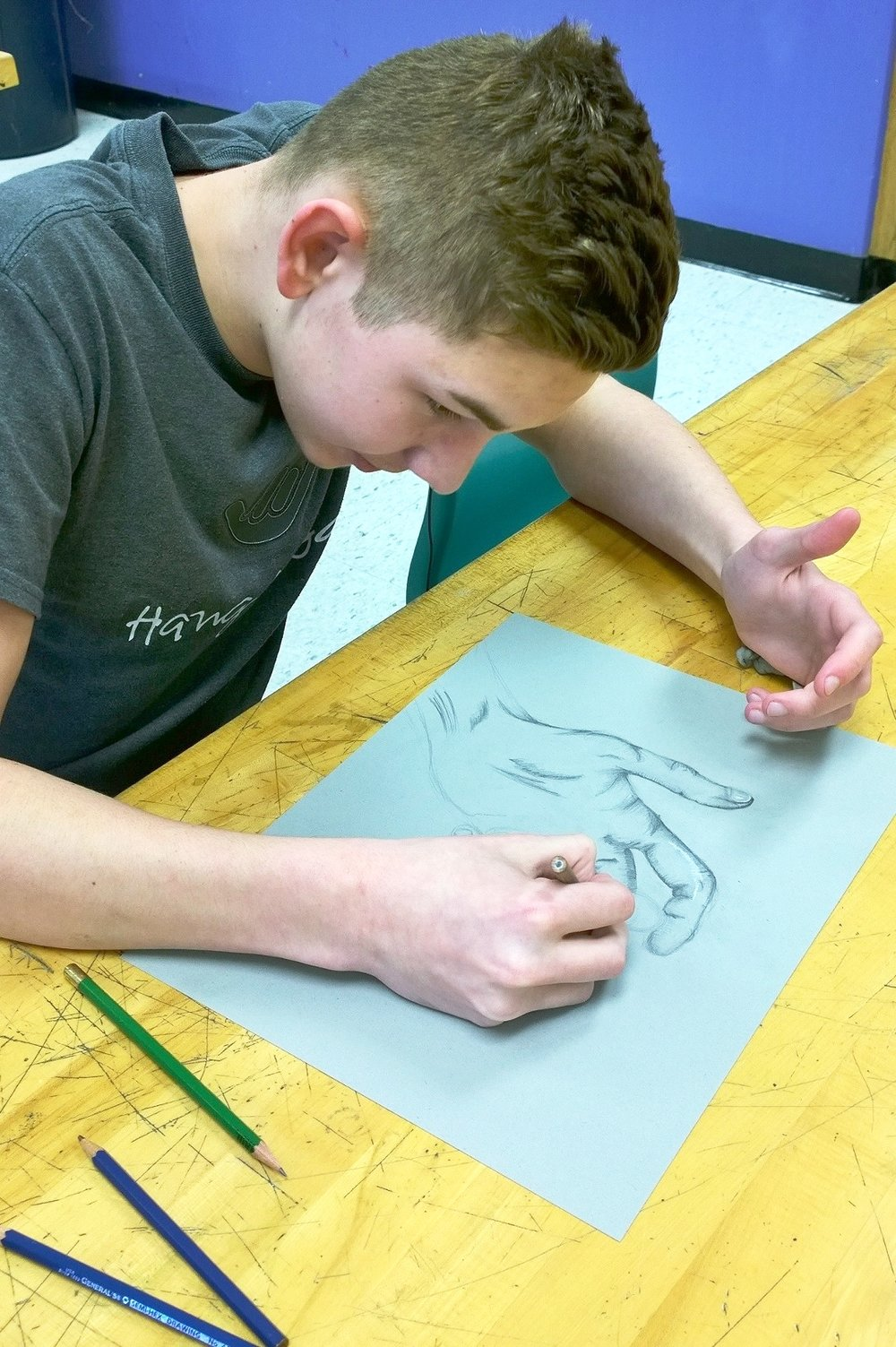 "Instructor Jean sent these photos of her CFAC class at North Oldham Middle School and said, ""All semester, we've been focusing on drawing hands. They are the most difficult part of the human body to draw accurately, so we started from the skeletal level and built on that. We will eventually create hands using different art movements. For example, next week we are starting a segment on Pop Art incorporating hands. For the last two weeks, we have been working on drawing, shading, and highlighting hands using toned paper, white charcoal, black charcoal, and different grades of graphite pencils."""