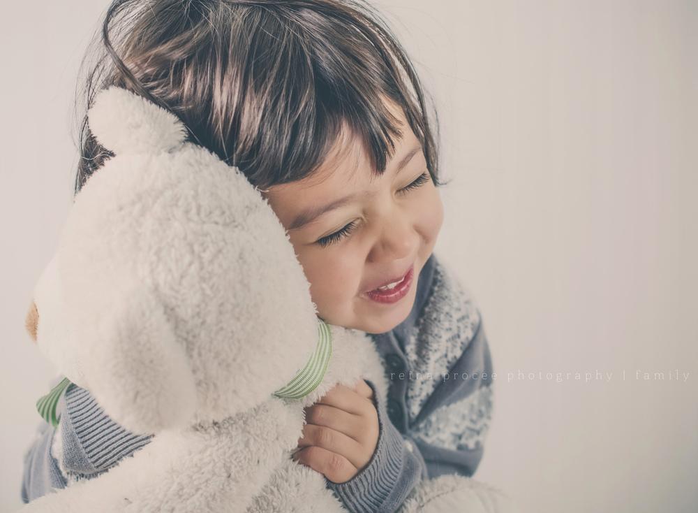 little girl with grey sweatshirt smiling and hugging teddy bear